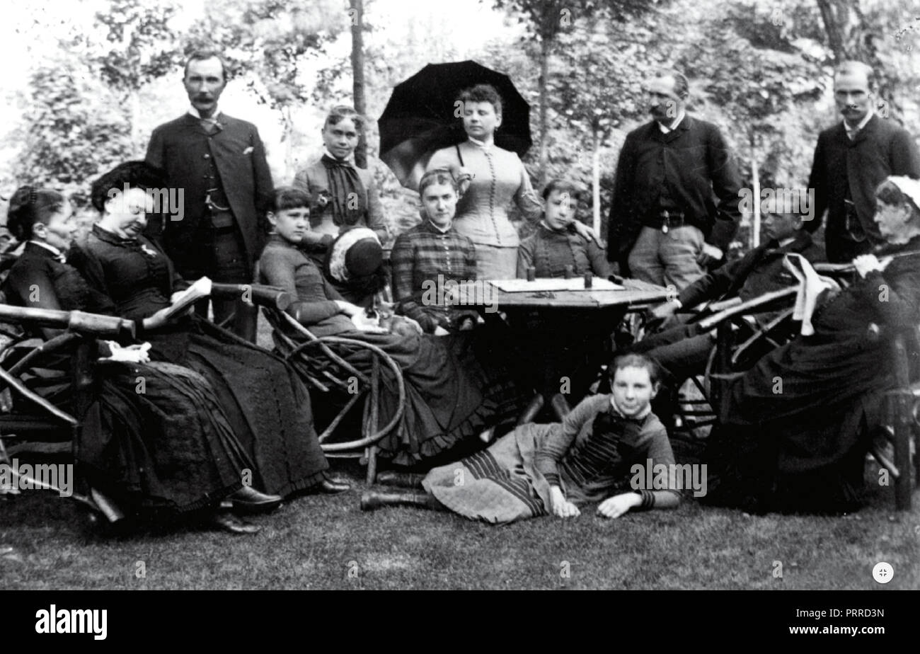 JOHN D. ROCKEFELLER (1839-1937) standing at right with family members and friends in Cleveland,Ohio, about 1880. His wife Laura is far left with daughters Edith and Bessie sitting behind the table and Alta lying on the grass. Laura's mother is at far right. - Stock Image