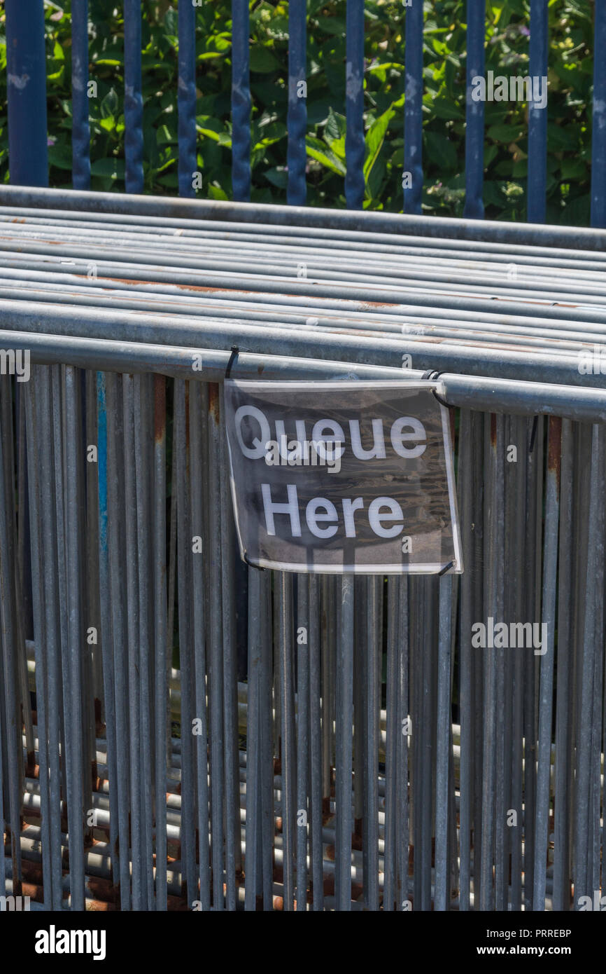 Stack of metal barriers with QUEUE HERE sign attached - metaphor for Wait in Line and also possible data bottlenecks, broadband bottlenecks. - Stock Image