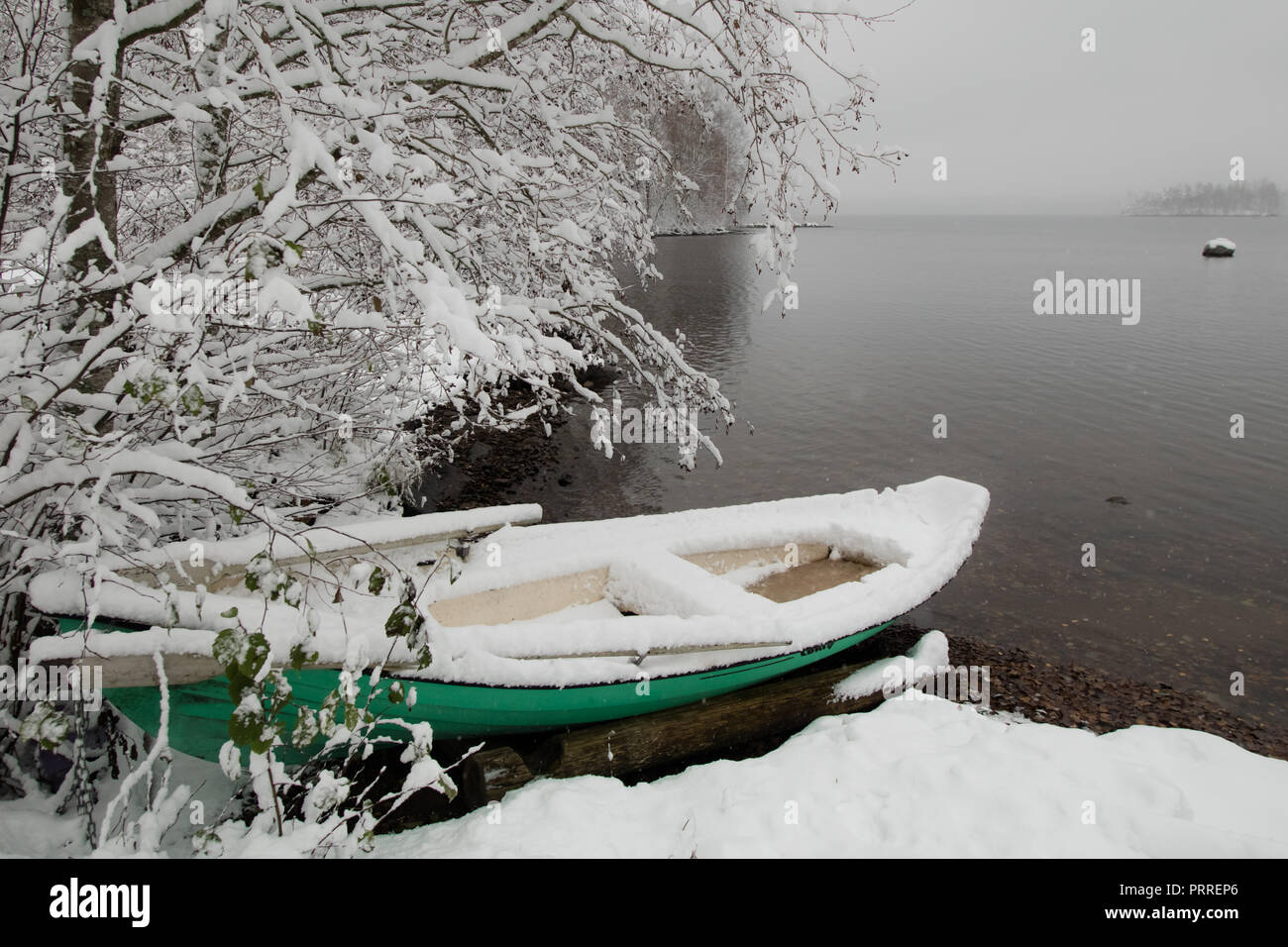Early first snow has arrived and surprised the boat owner of this green rowing boat - Stock Image