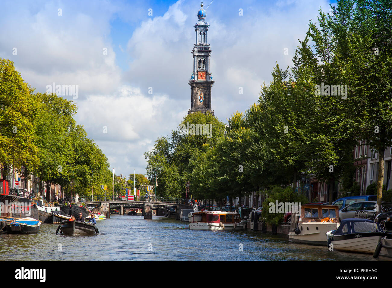 Boats on Prinsengracht, behind the tower of Westerkeerk, Amsterdam, The Netherlands - Stock Image