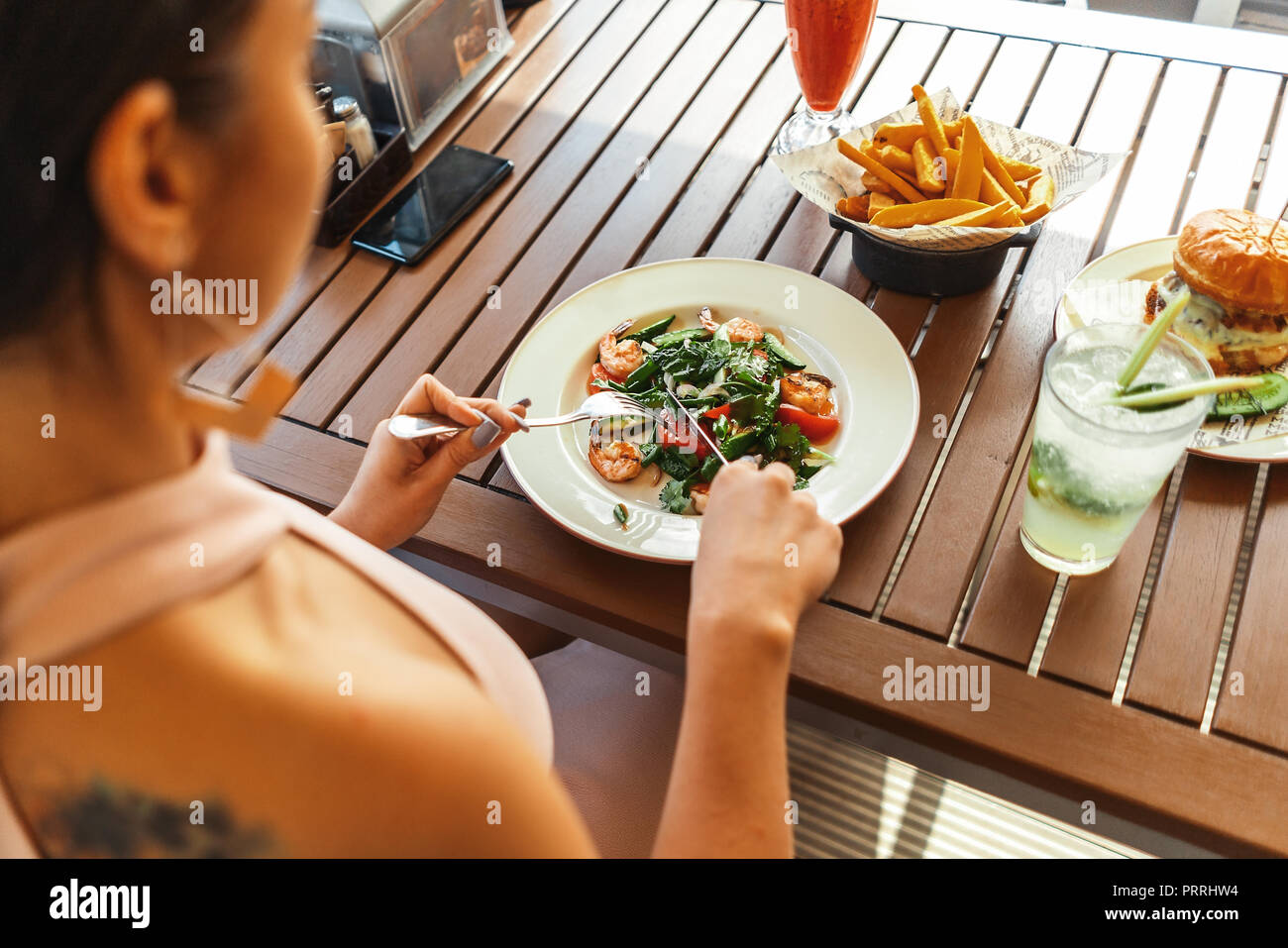 Close up of young attractive woman eating salad at street cafe. - Stock Image