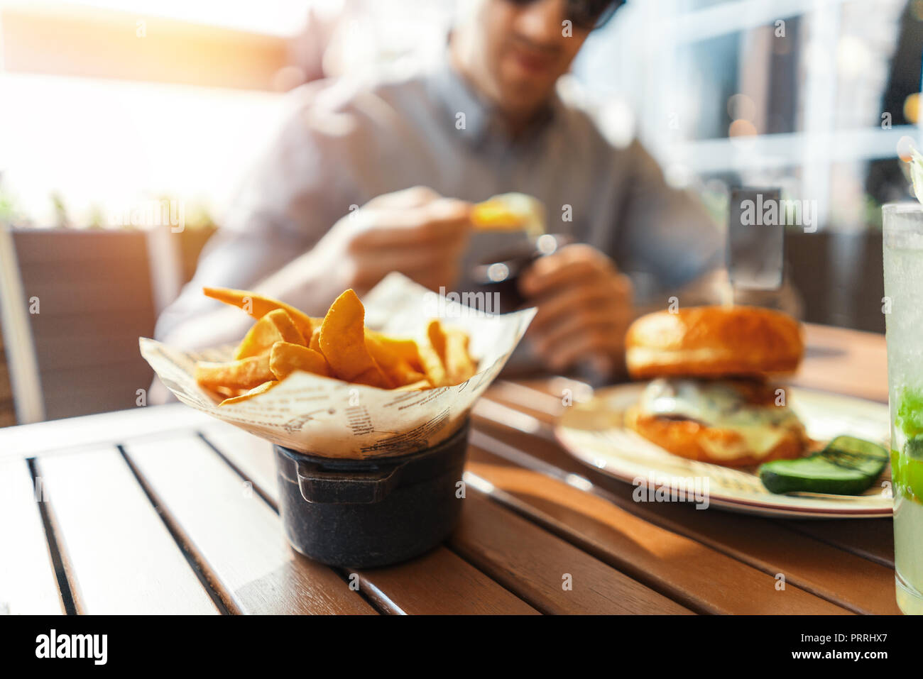 Close up of young attractive man eating french fries and burger at street cafe. - Stock Image
