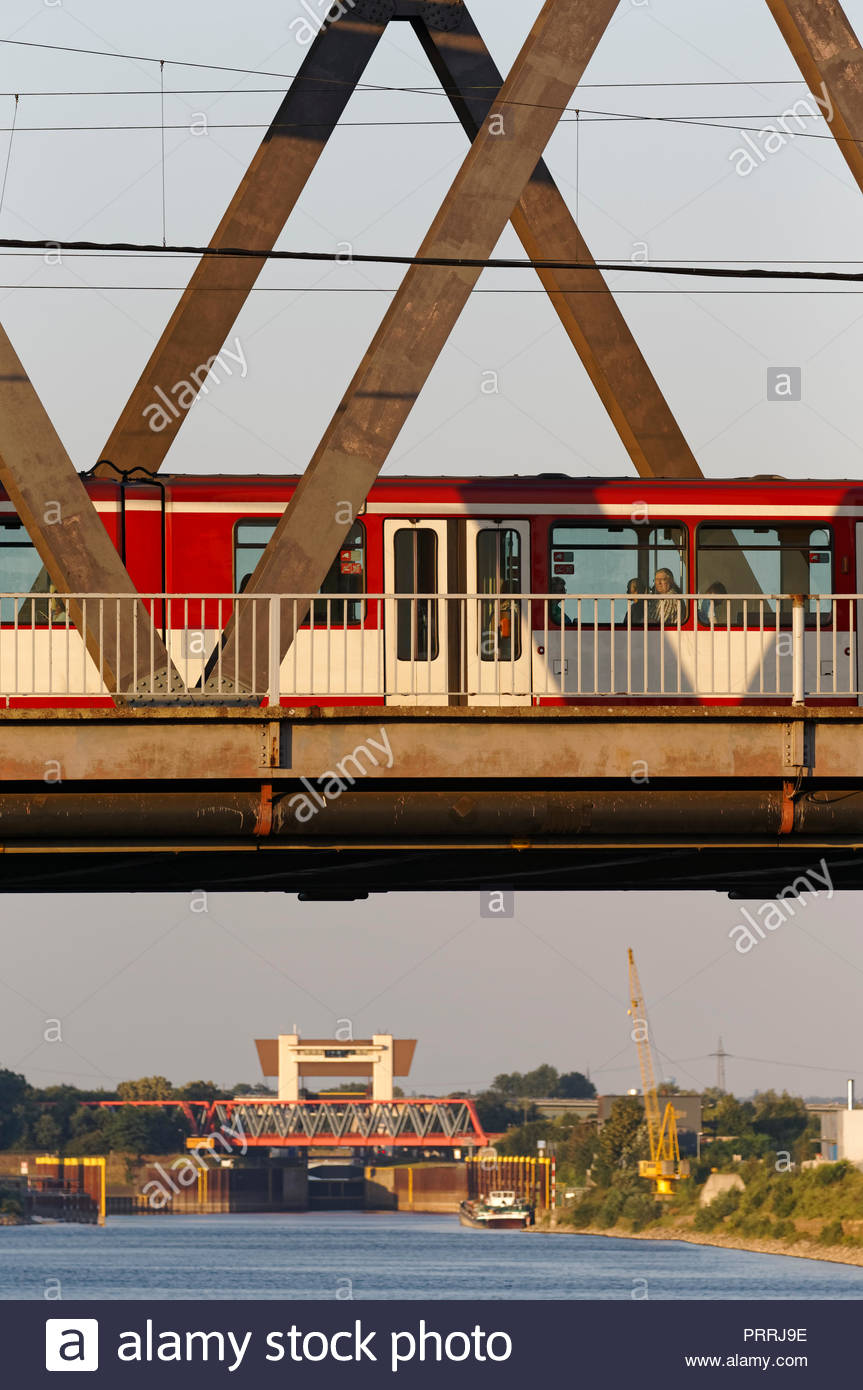 Duisburg Meiderich truss bridge with tram streetcar crossing Rhine-Herne-Canal waterway lock sluice gate tower water traffic transport inland port - Stock Image