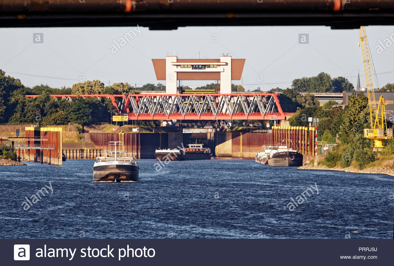 Duisburg Meiderich lock sluice gate tower control platform red bridge crossing canal waterway Rhine-Herne-Canal inland port cargo boat ship leaving - Stock Image