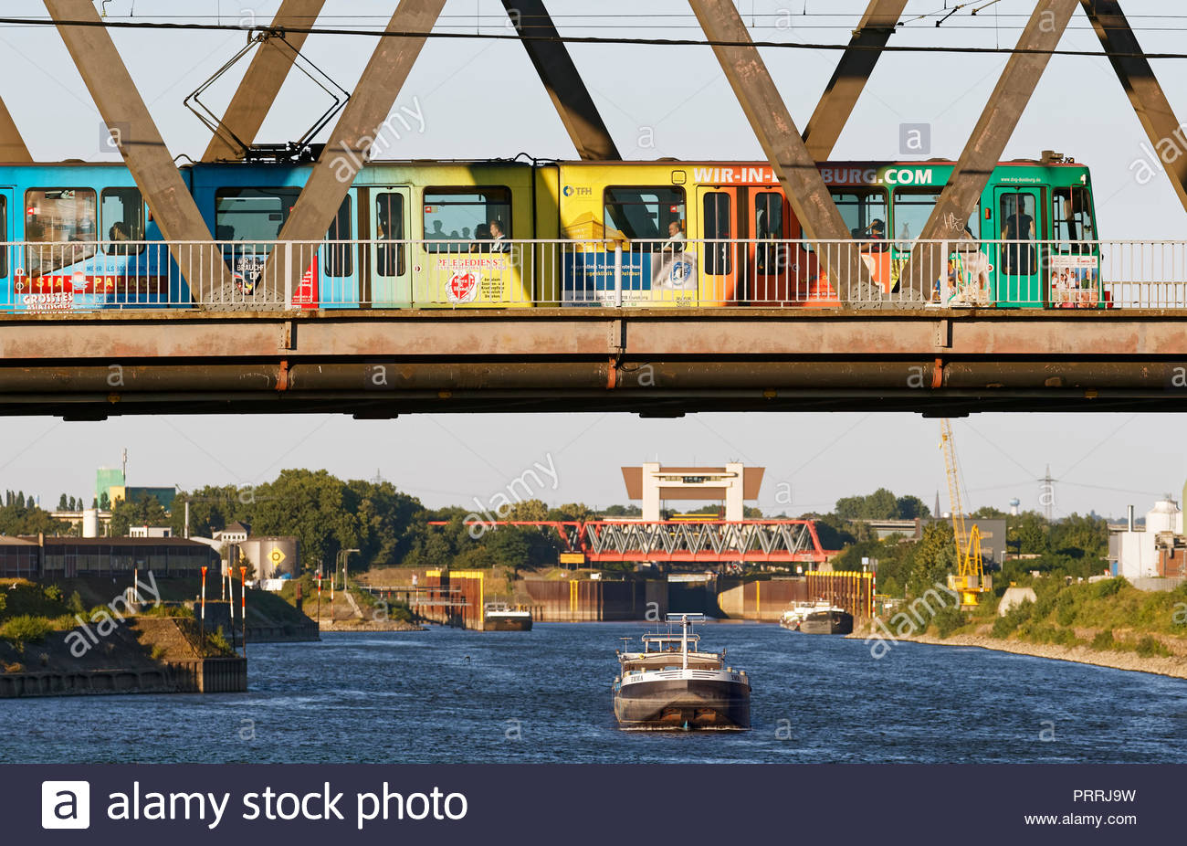 Duisburg Meiderich truss bridge tram streetcar crossing Rhine-Herne-Canal waterway cargo boat lock sluice gate tower water transport inland port - Stock Image