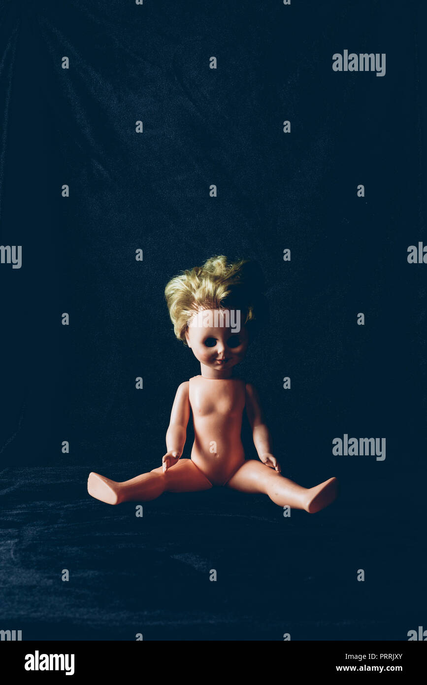 creepy doll sitting in darkness, frightening halloween decor - Stock Image
