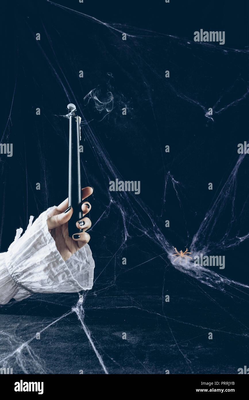 cropped view of mystic woman holding smoky candle in darkness with spider web - Stock Image