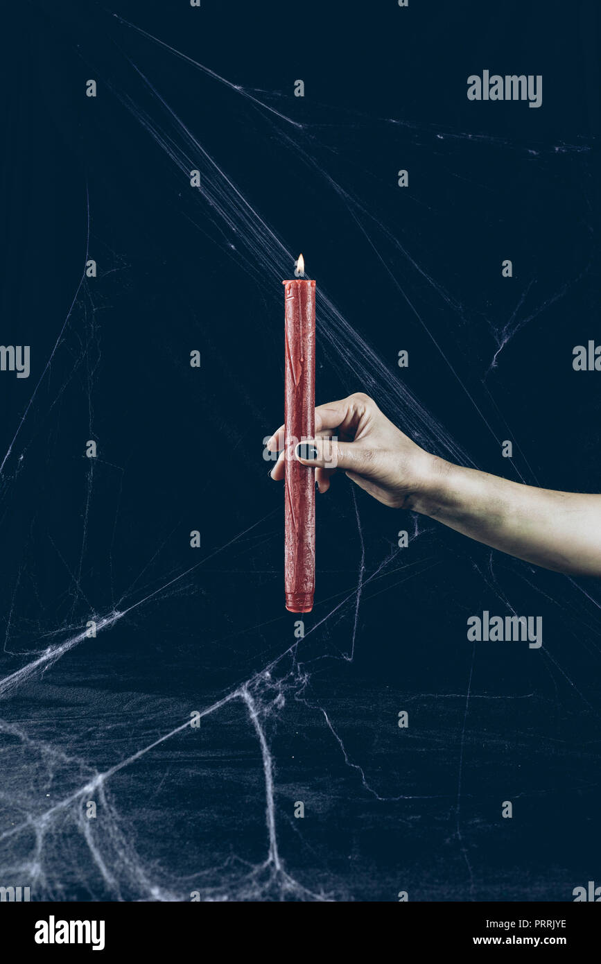 cropped view of gothic woman holding red candle in darkness with spider web - Stock Image