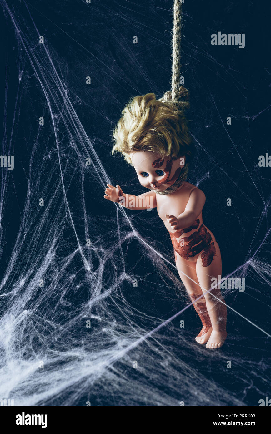 creepy dirty doll hanging noose in darkness with spider web - Stock Image