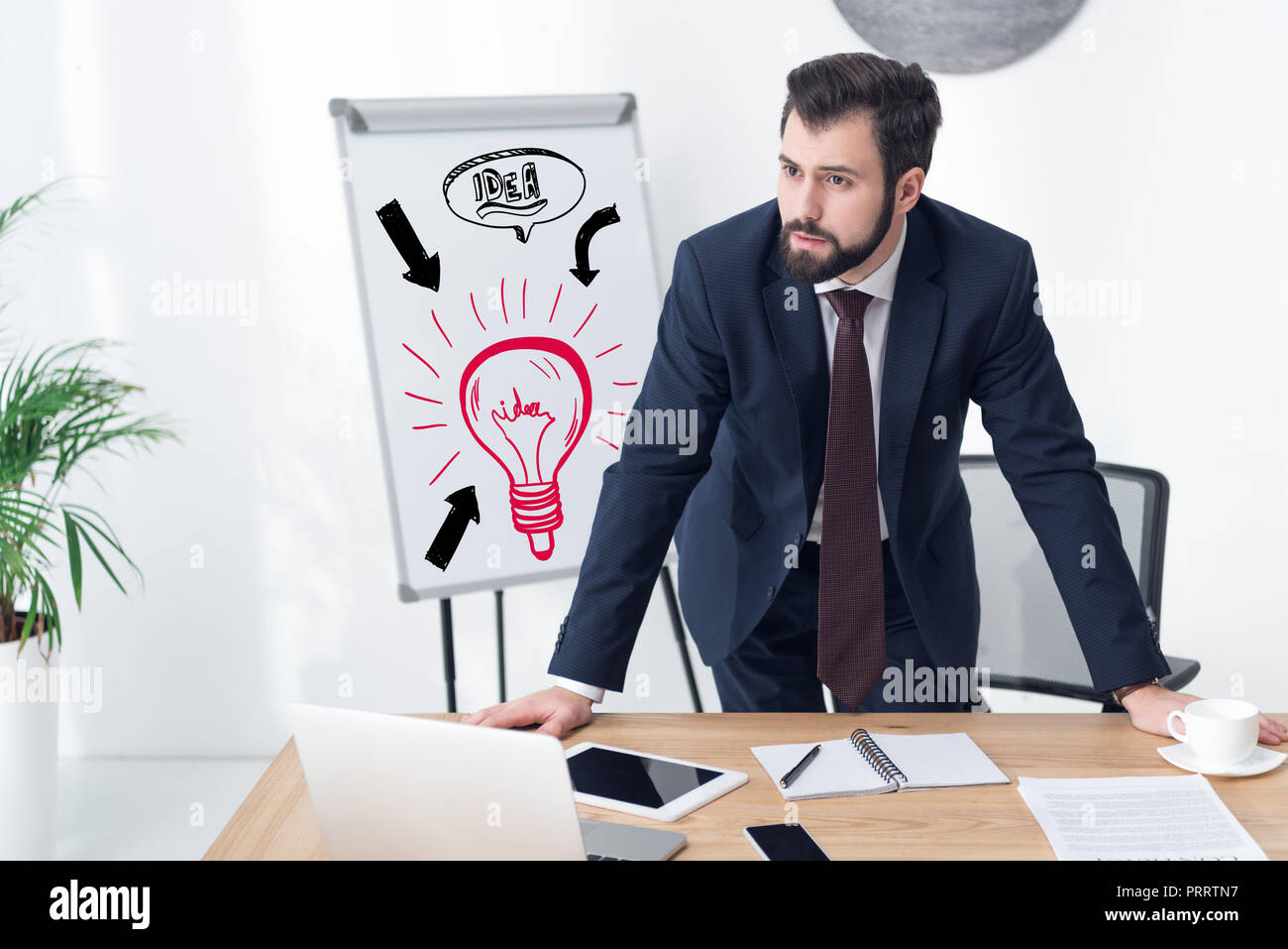 pensive businessman looking away at workplace in office with idea inscription and light bulb icon on whiteboard Stock Photo