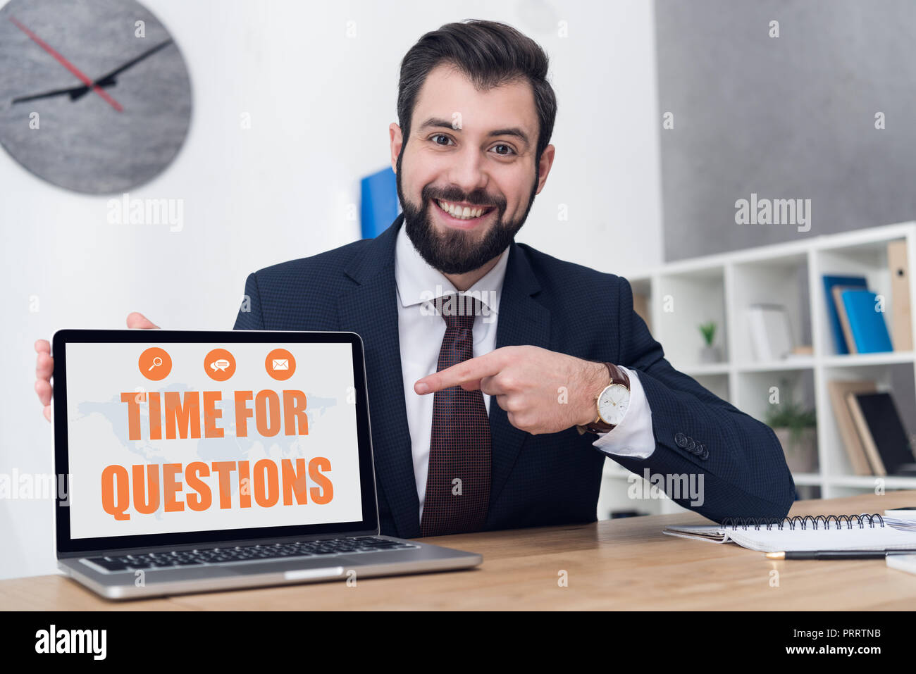 portrait of cheerful businessman pointing at laptop with time for questions inscription at workplace in office Stock Photo