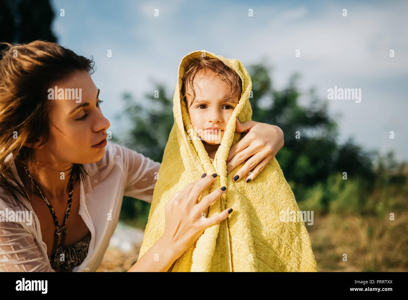 mother covering daughter with towel after swimming in water - Stock Image