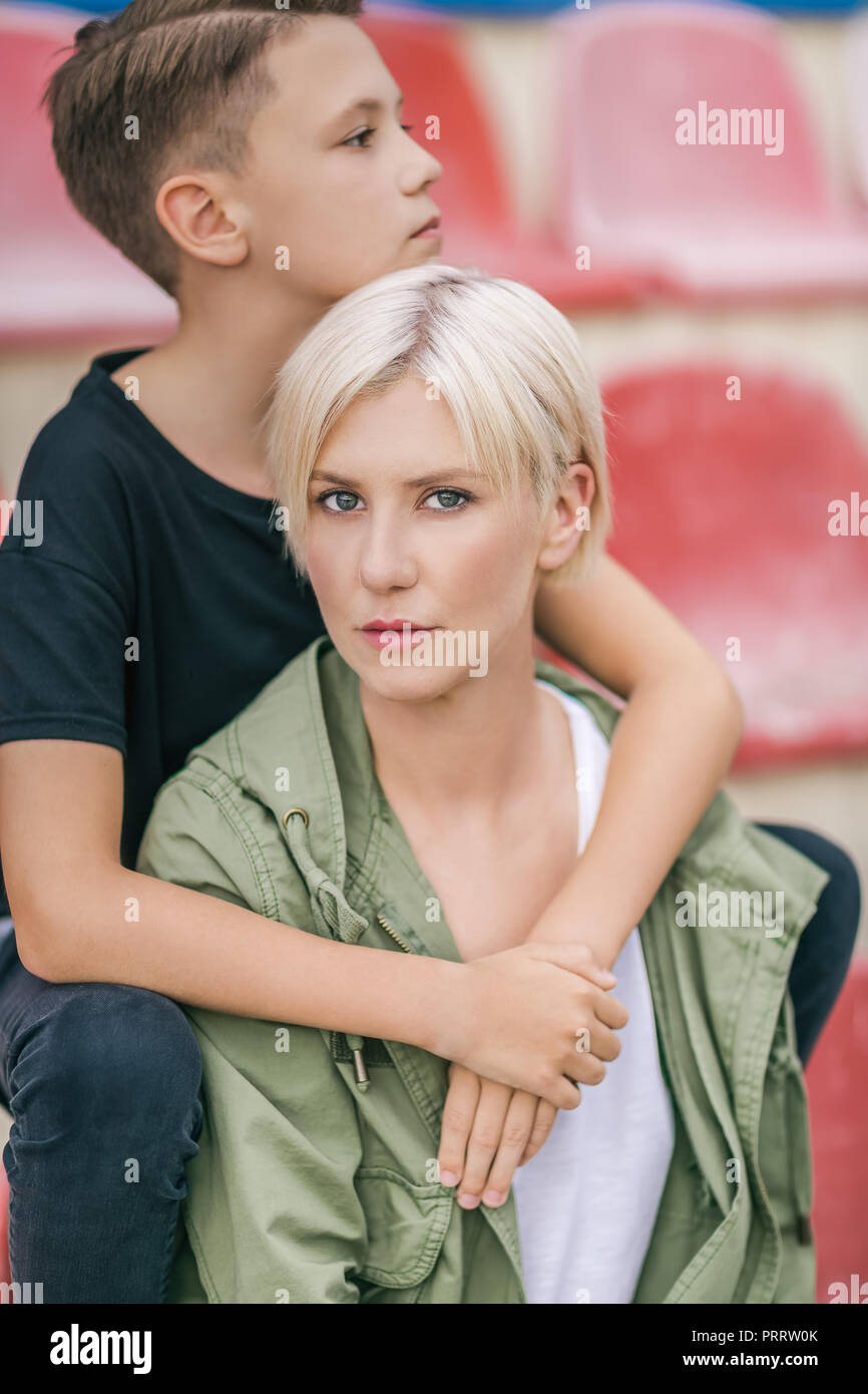 beautiful preteen boy hugging mother while sitting together on stadium - Stock Image