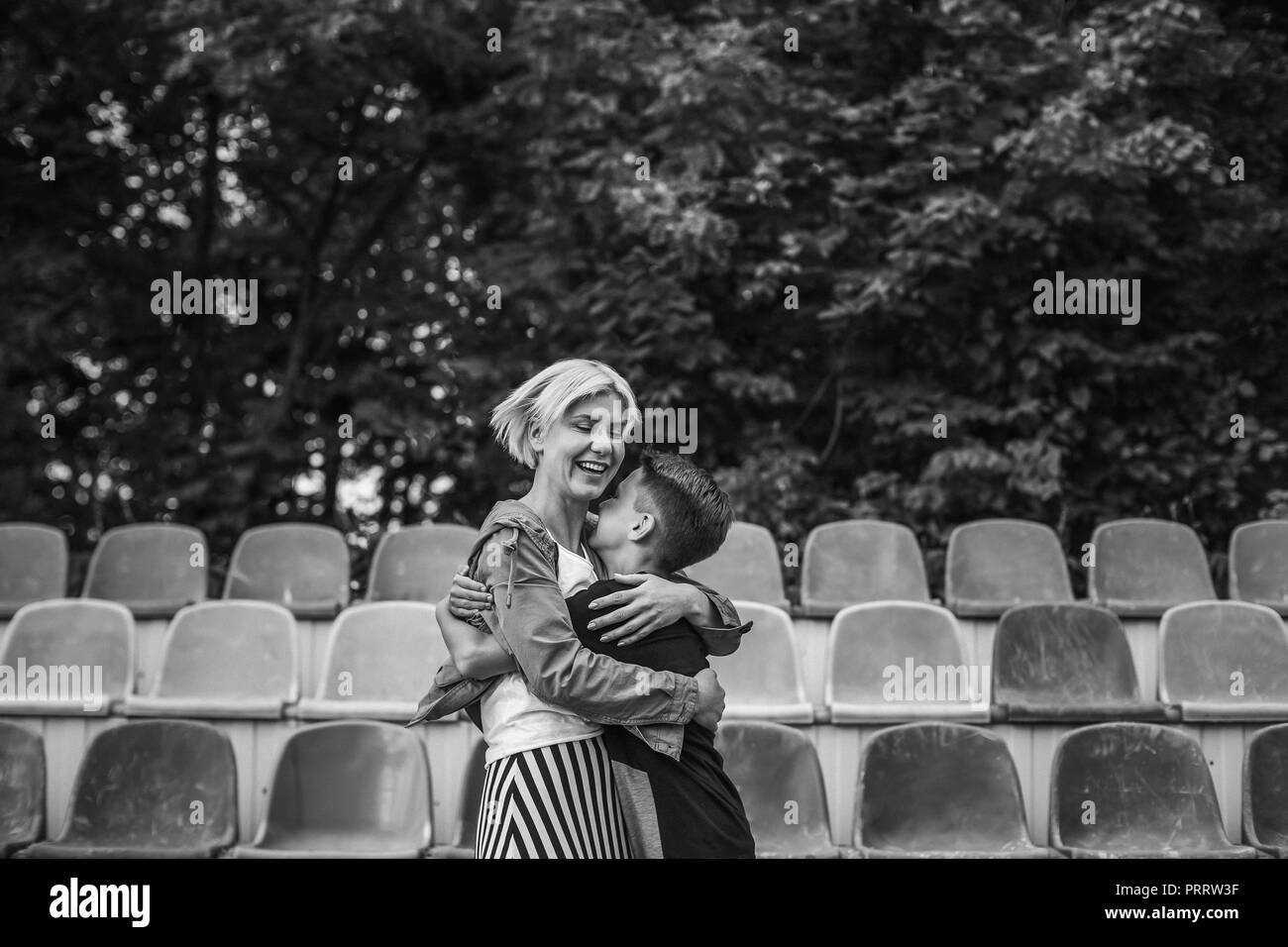 happy mother and son hugging on stadium, black and white photo - Stock Image