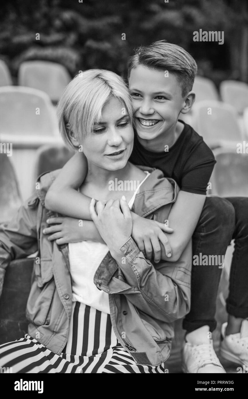 black and white photo of happy mother and son hugging while sitting on stadium seats - Stock Image