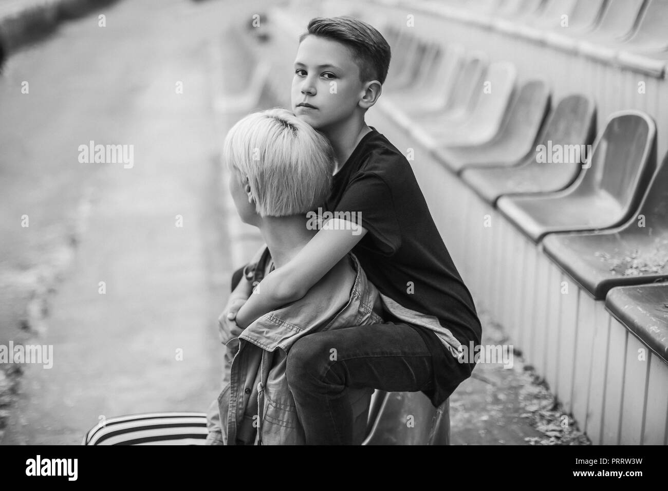 black and white photo of mother and son hugging on stadium - Stock Image