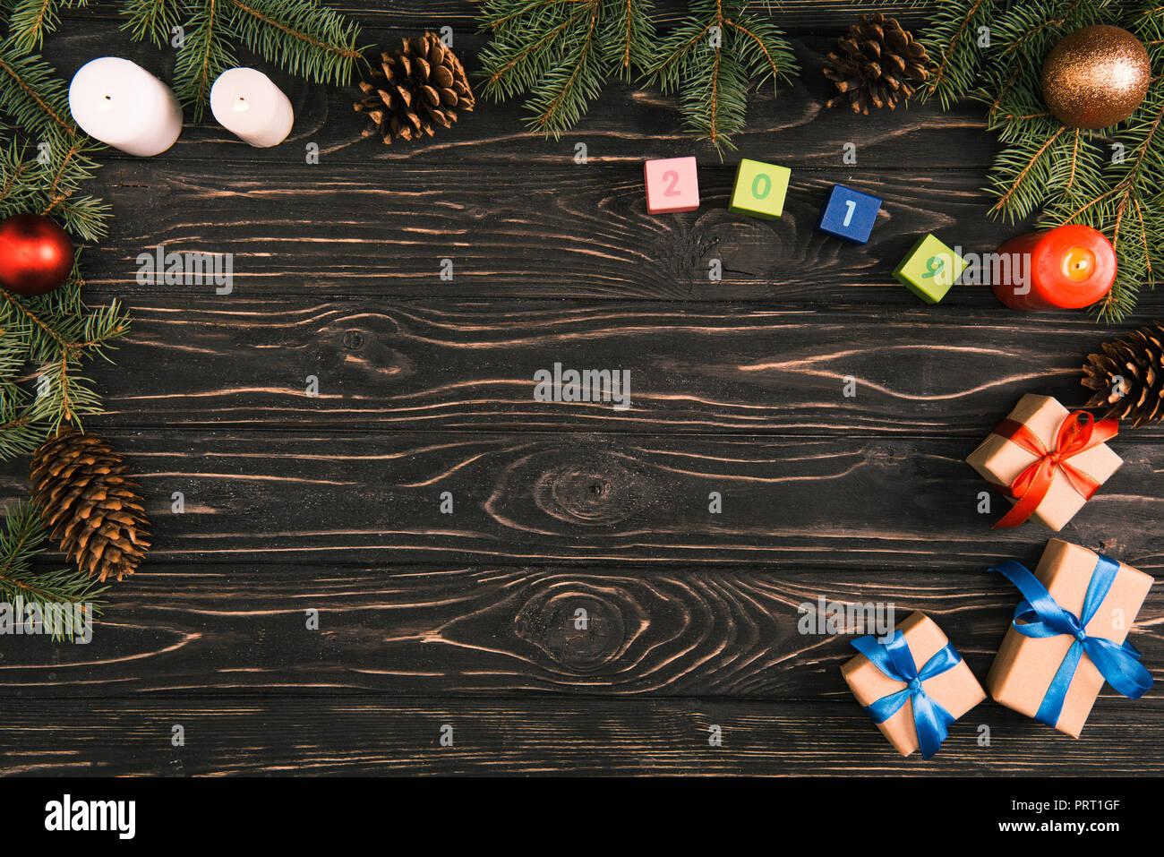 top view of 2019 symbol on cubes christmas gifts candles and fir twigs with