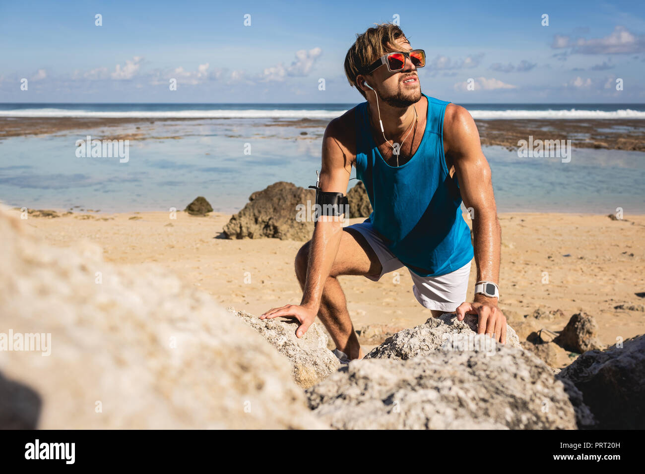 sportsman looking up while climbing on rocks on beach, Bali, Indonesia - Stock Image