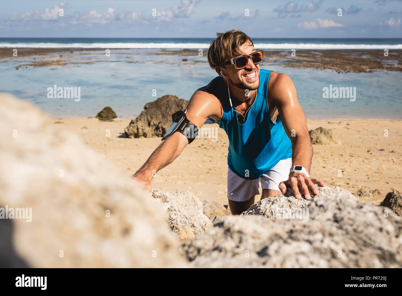 smiling sportsman climbing on rocks on beach, Bali, Indonesia - Stock Image