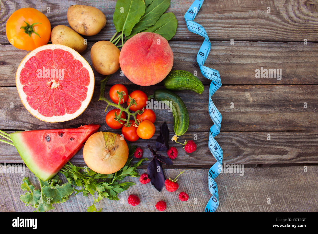 Fruits, vegetables and in measure tape in diet on wooden background - Stock Image