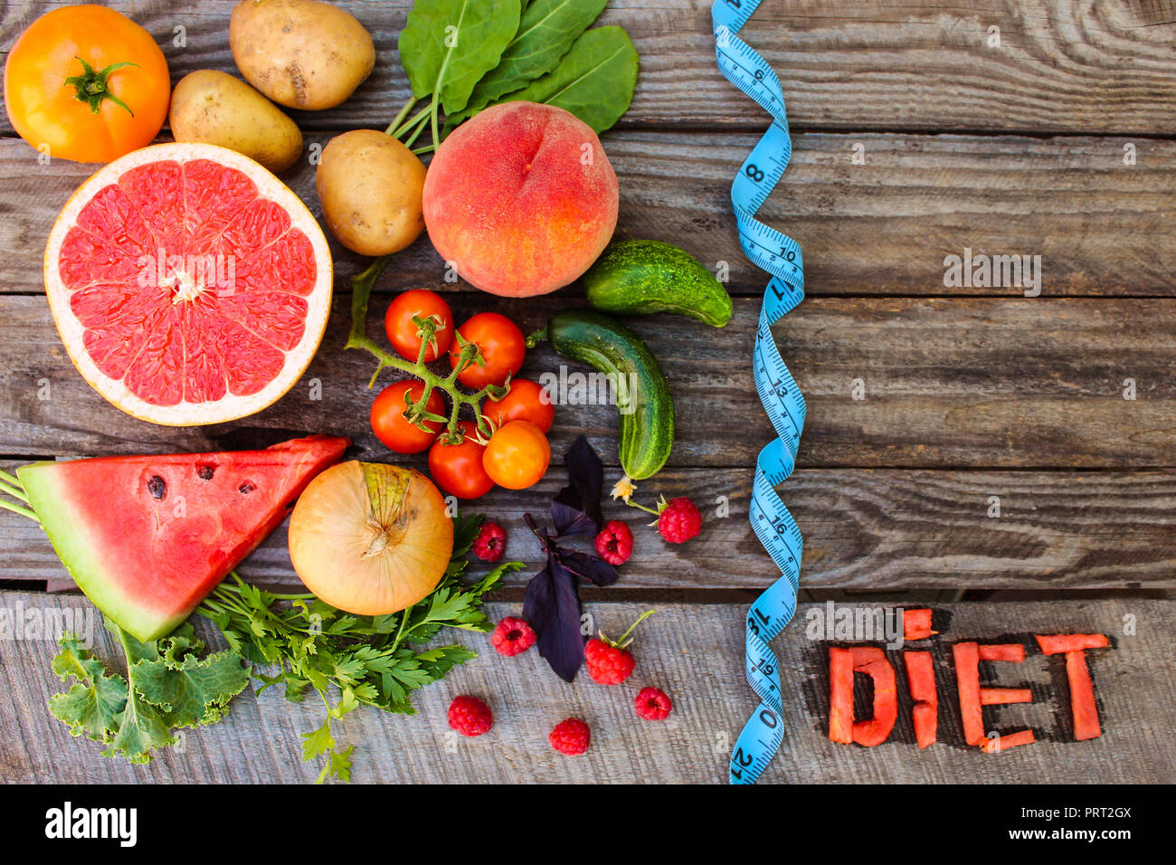 Fruits, vegetables and in measure tape in diet on wooden background. word diet written in English slices of watermelon. - Stock Image