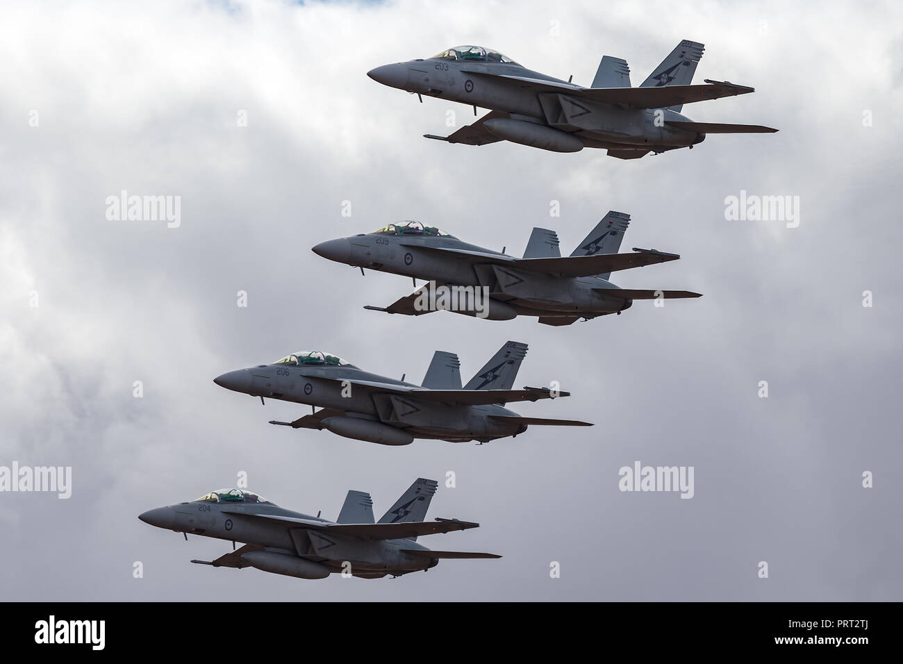 Four Royal Australian Air Force (RAAF) Boeing F/A-18F Super Hornet multirole fighter aircraft flying in formation. - Stock Image