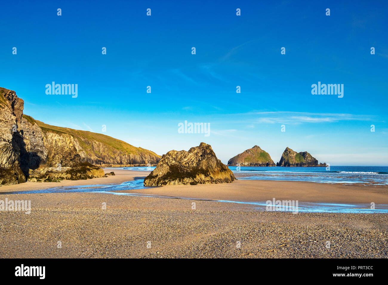Rocks on Holywell Beach, with a view through  of the off shore Carters Rocks, Cornwall, UK Stock Photo