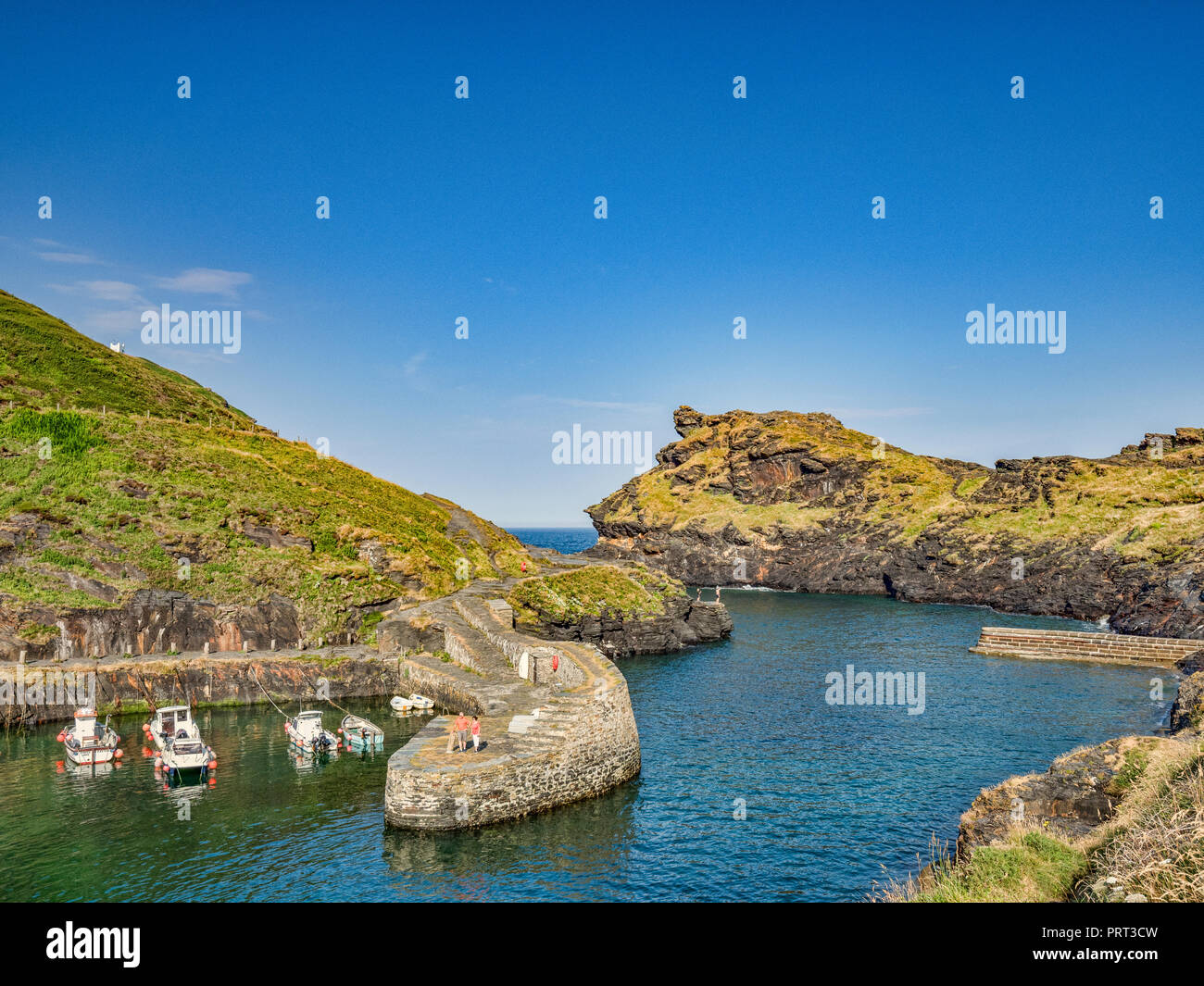 2 July 2018: Boscastle, Cornwall, UK - A couple admire the view of the harbour and its stunning rock formations from the breakwater. Stock Photo
