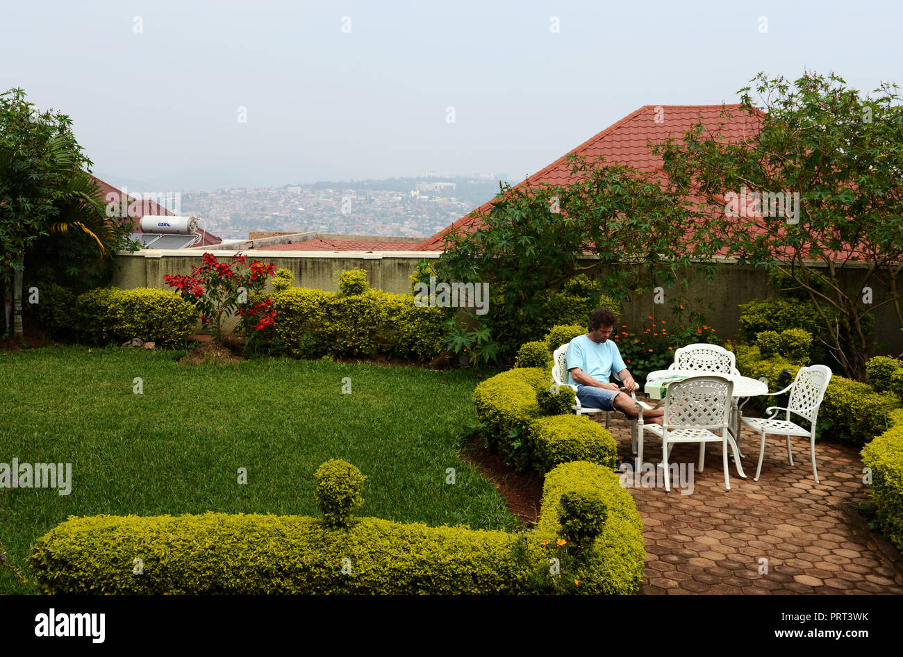 A tourist resting in the beautiful garden of the Yambi hotel in Kigali. - Stock Image