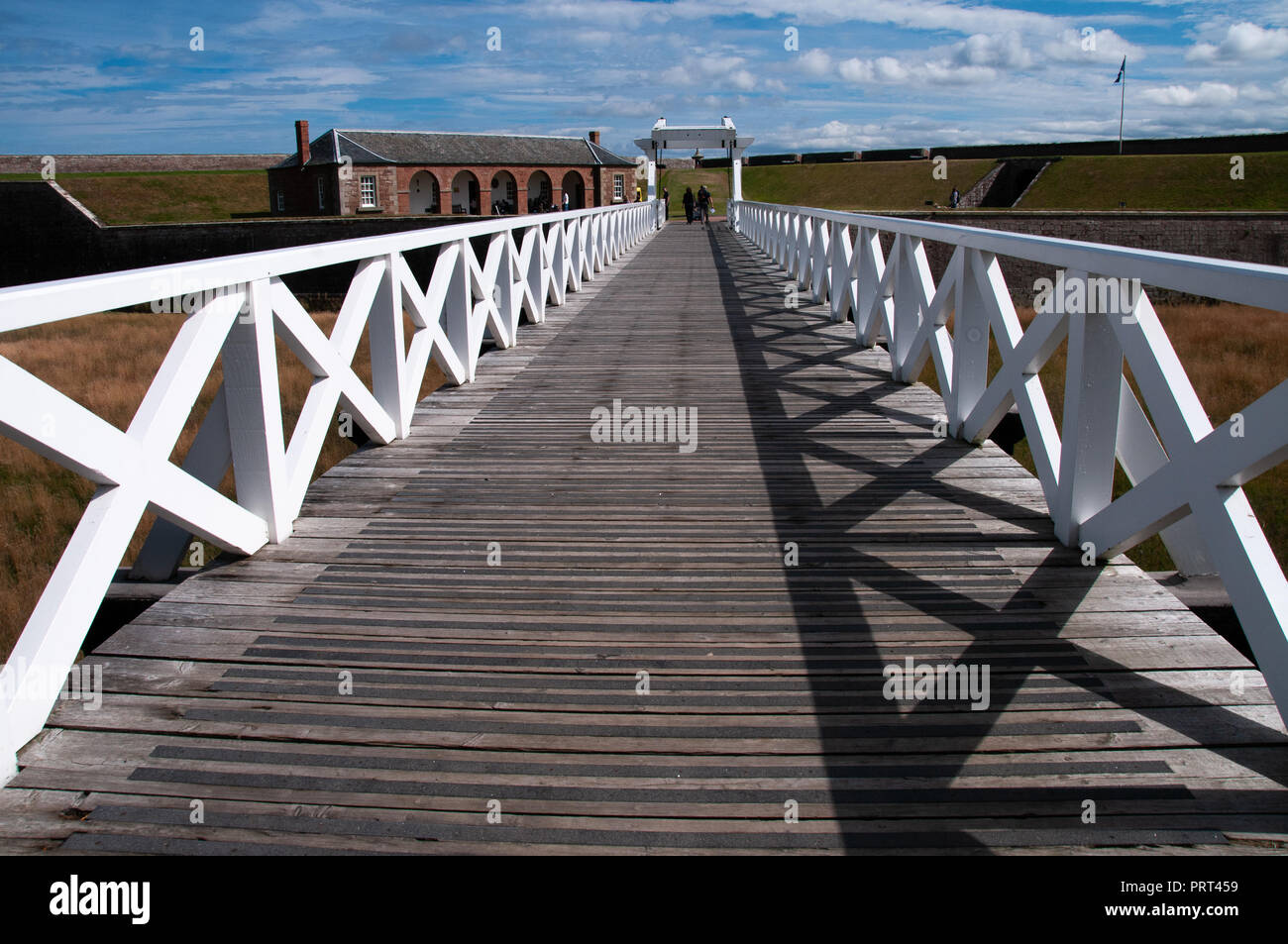white rail crosses of the leading lines entrance bridge to Fort George, 18th century fortress near Inverness, Scotland in the sunshine - Stock Image
