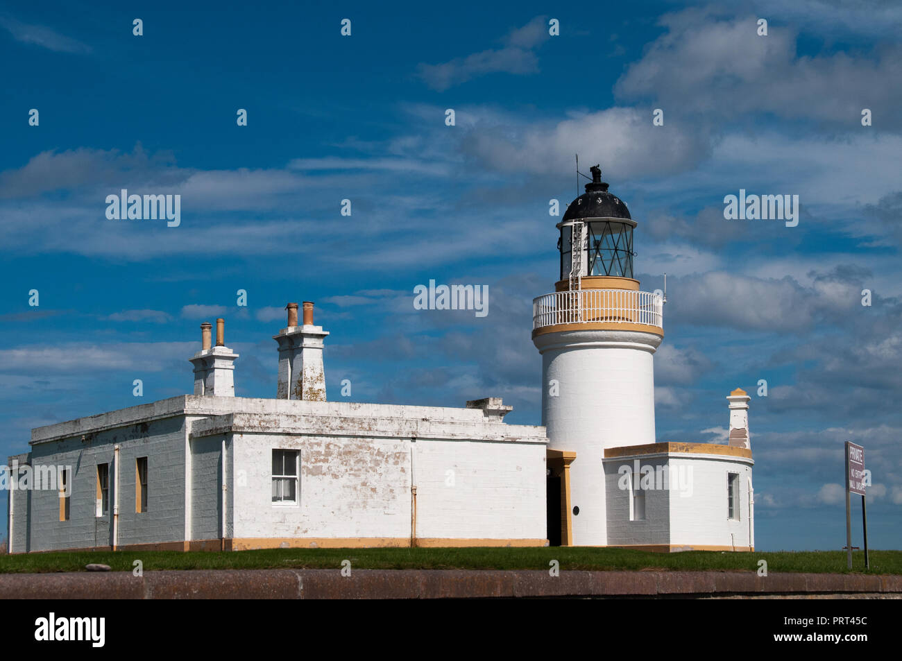 Bright white square Chanonry Point Lighthouse, Fortrose, Inverness against a blue and cloudy sky. - Stock Image
