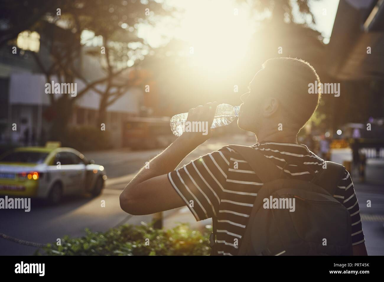 Young man drinking water from bottle during walk on street at sunset. - Stock Image
