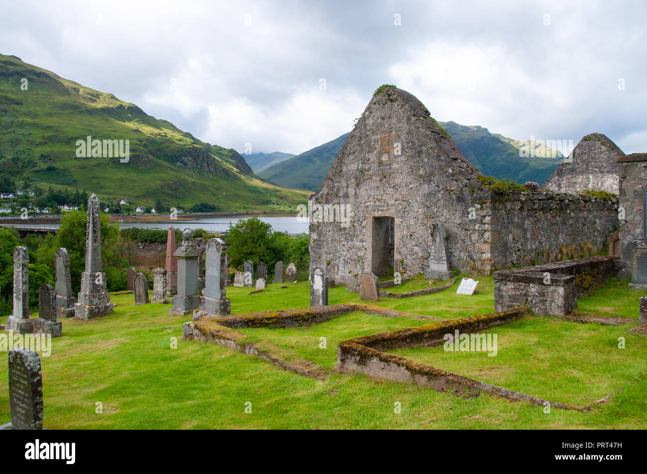 Crumbling stone ruins of barns, stone walls and old gravestones on a bank above still water, in the Scottish Highlands - Stock Image