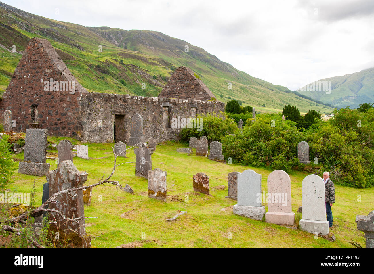 old man looking at a grave in crumbling stone ruins of barns, stone walls and old gravestones on a bank above still water, in the Scottish Highlands - Stock Image