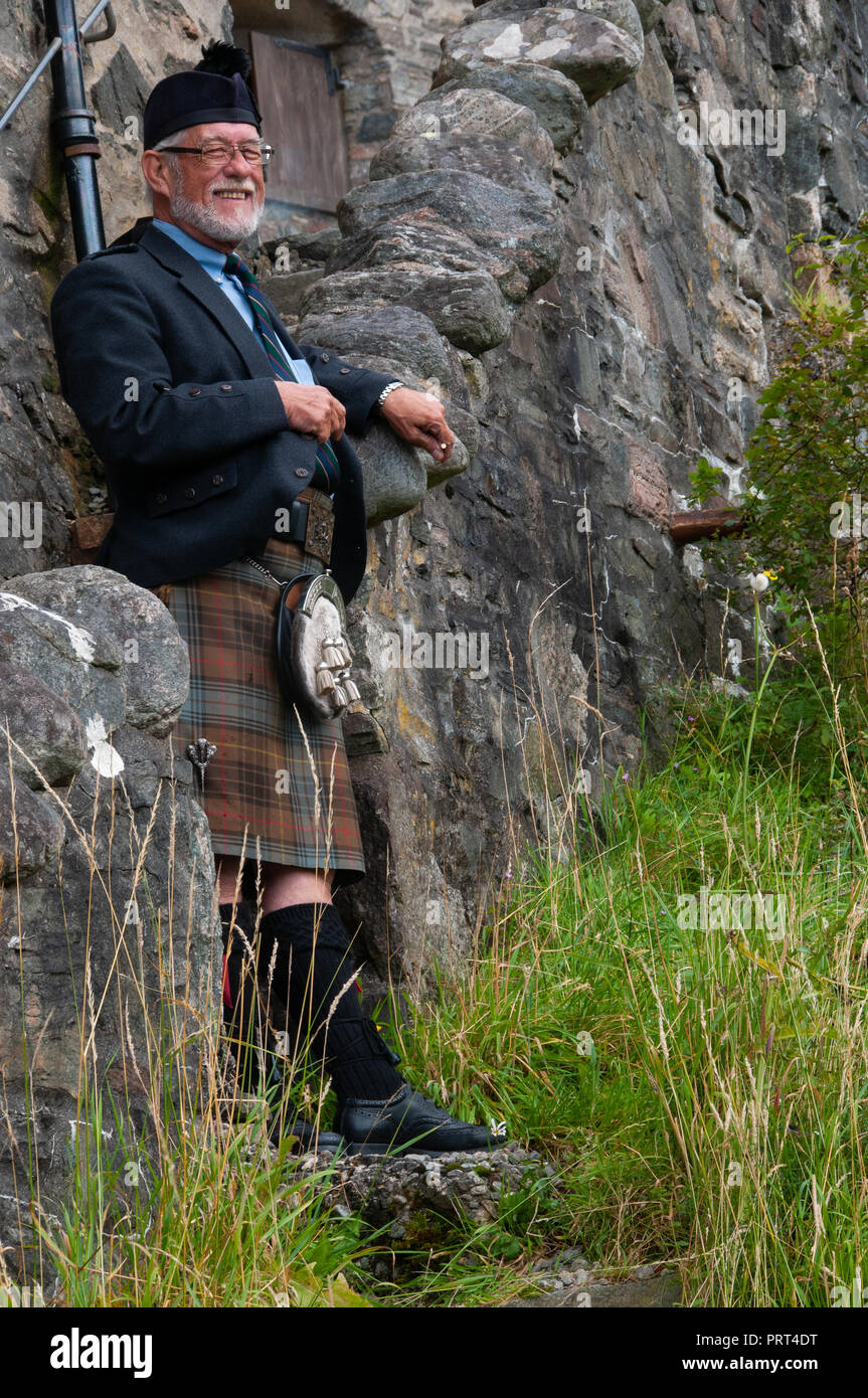 Part of Eileen Donan historic house and castle of the MacRae family on shores of Kyle of Lochalsh, featuring a mature Scot in full highland dress. - Stock Image