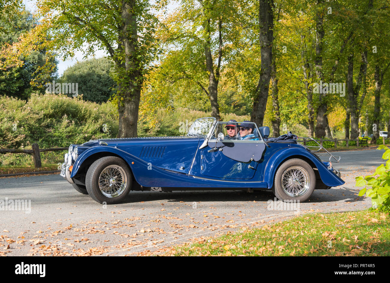 Morgan Plus 4, a blue convertible open top car with 2 passengers and the roof down, on a country road in the UK. Morgan Plus Four cars. - Stock Image