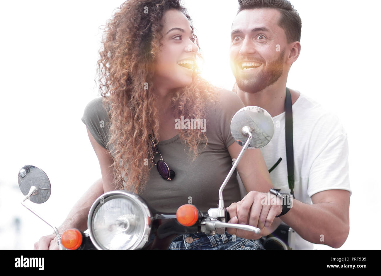 Attractive couple riding a scooter on a sunny day in the city - Stock Image