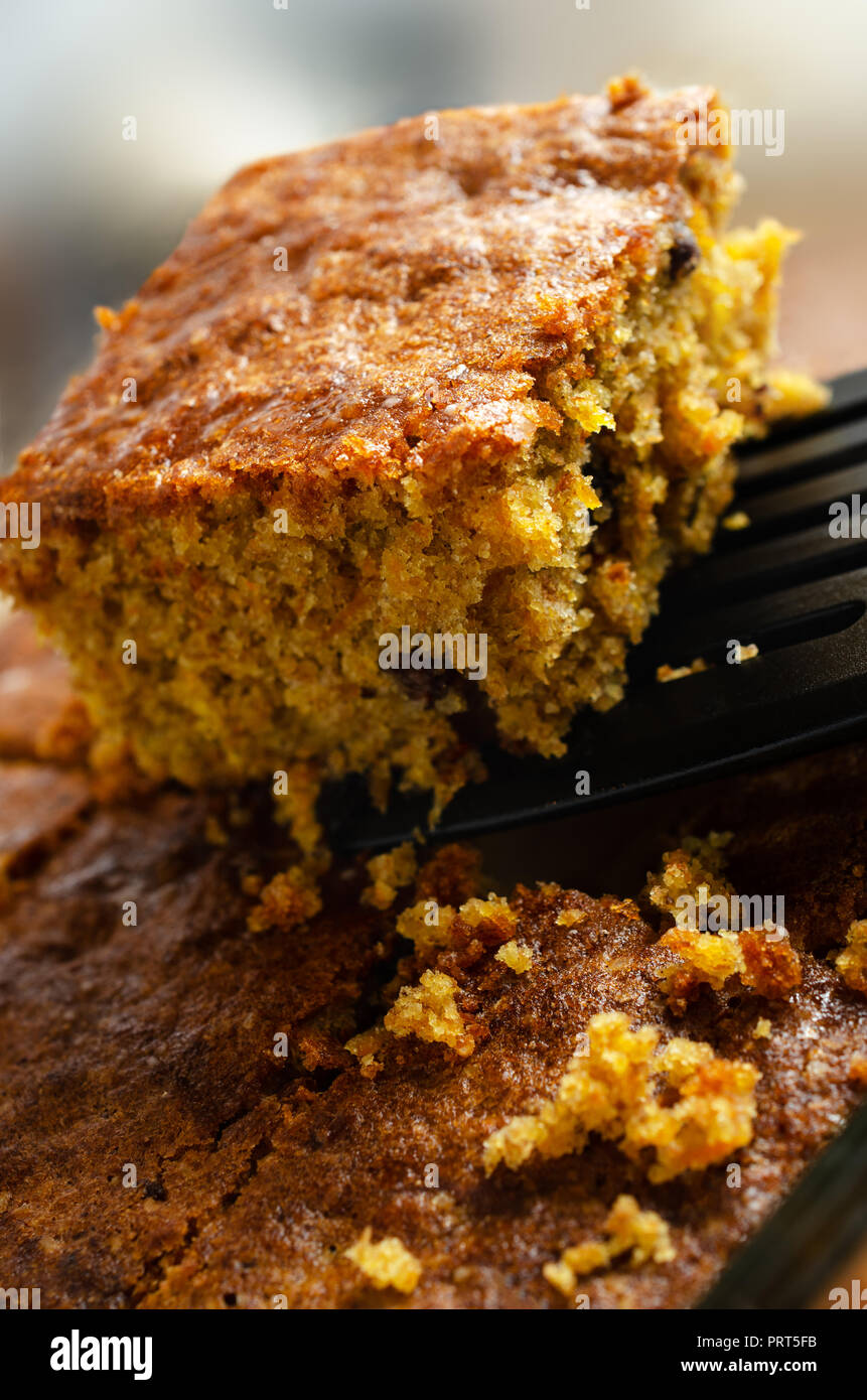 A slice of carrot cake, lifted out of baking dish with remainder and crumbs below. Close up side corner view. - Stock Image
