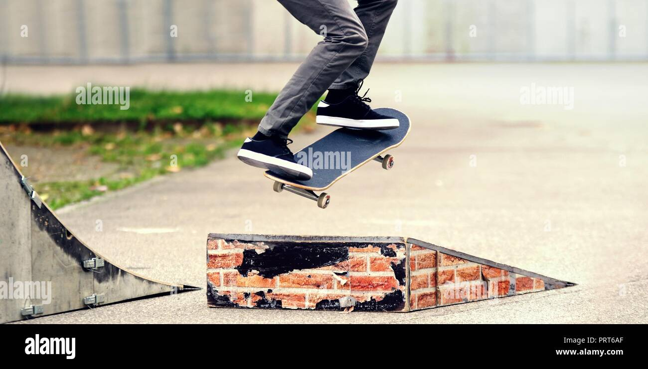 Young skateboarder practicing in the skate park. - Stock Image