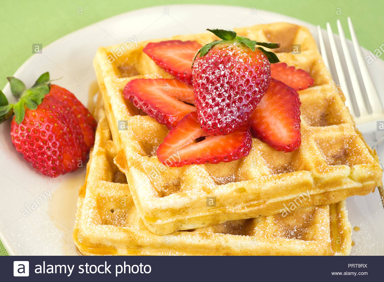 Delicious homemade waffles and fresh strawberries, Canadian Maple syrup and lightly dusted with confectioner's sugar. - Stock Image