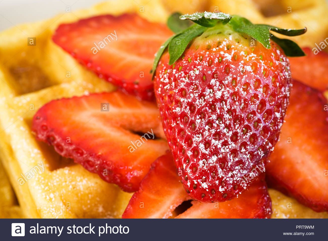 Delicious homemade waffles and fresh strawberries lightly dusted with powdered sugar. - Stock Image