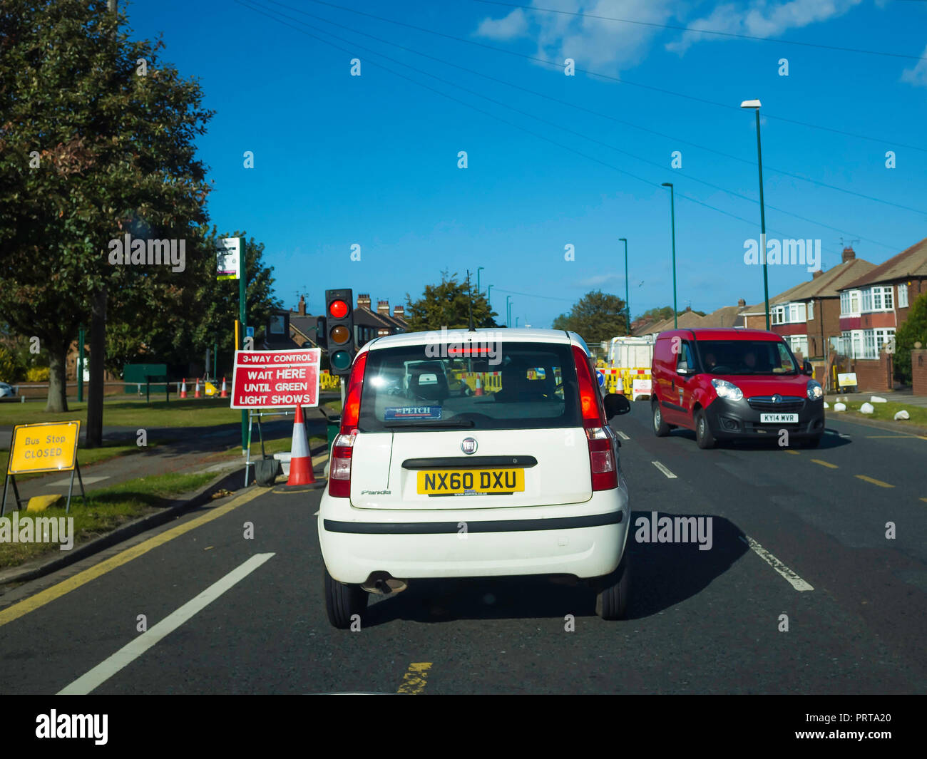 CA three way Traffic light controlled entrance to single lane road working during road works sign Wait Here Until Green Light Shows - Stock Image
