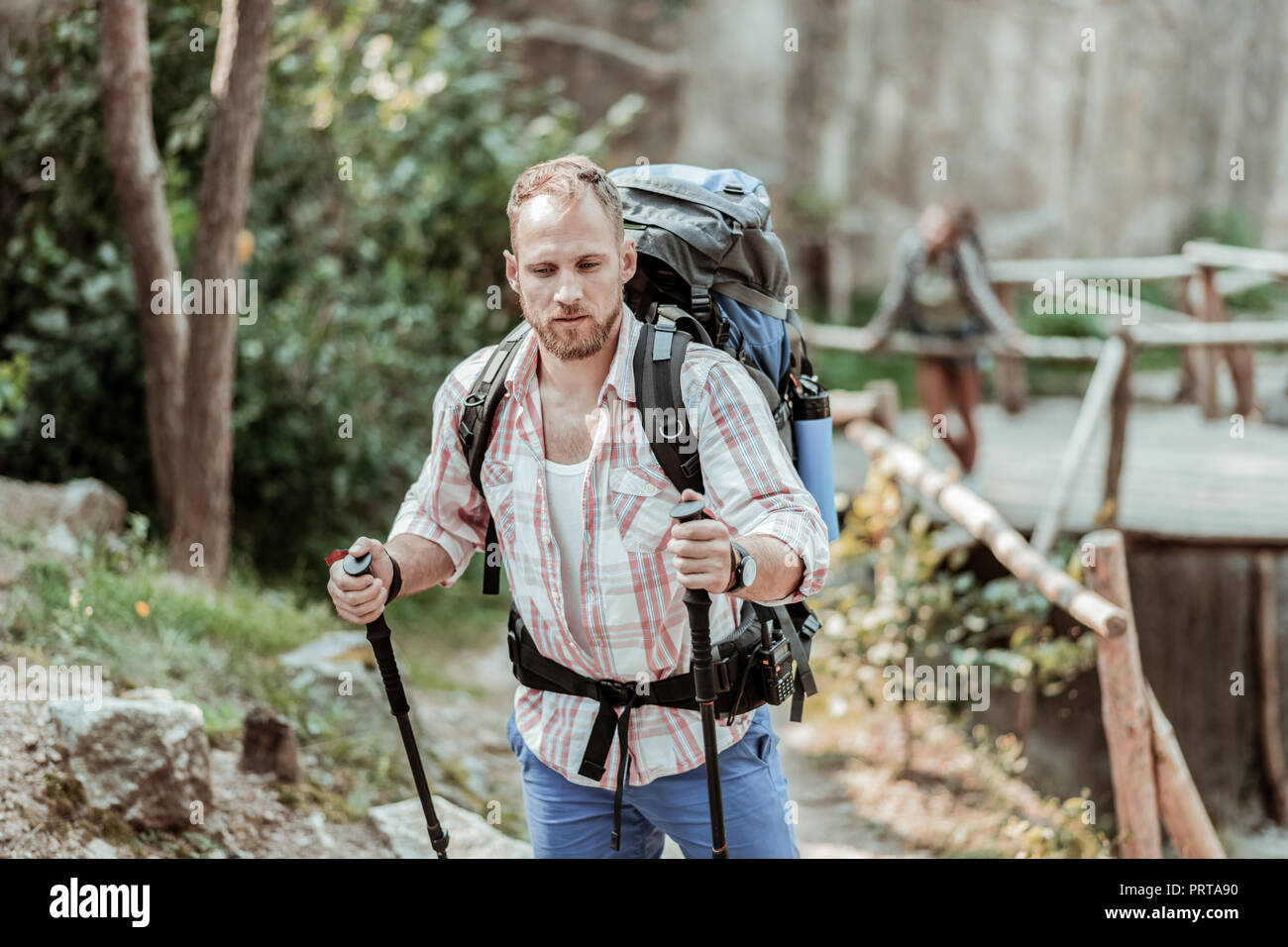 Handsome bearded blonde-haired man enjoying his weekend with walking poles - Stock Image