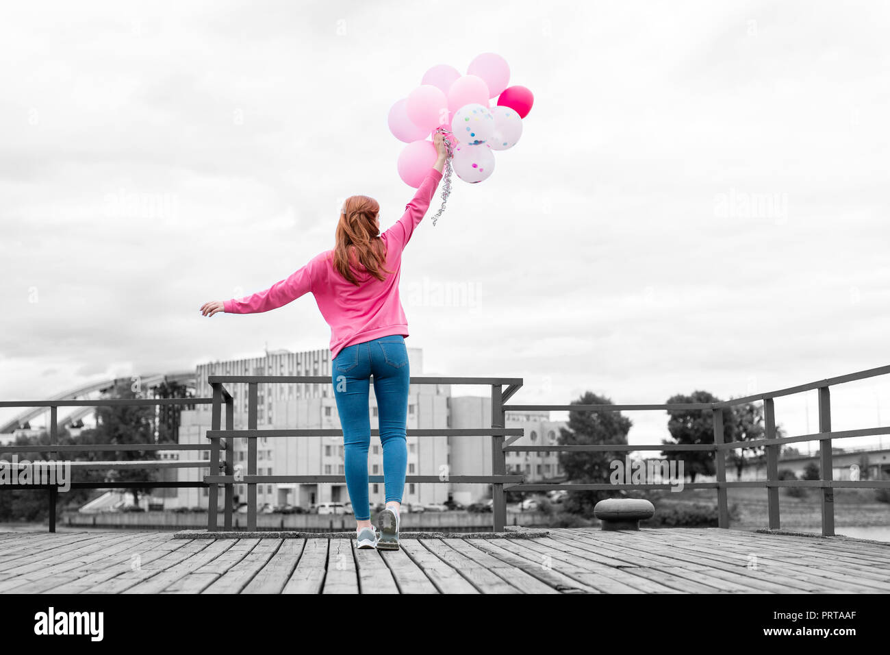 Relaxed young girl putting pink balloons up while standing on the pier - Stock Image
