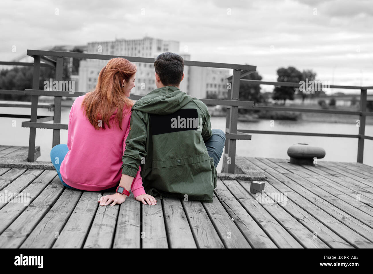 Two people sitting on the pier and having god time - Stock Image