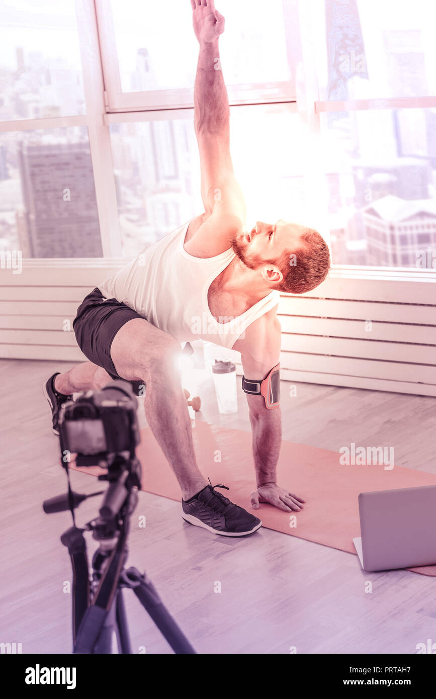 Hardworking sportsman keeping his hand up while doing stretching at home Stock Photo