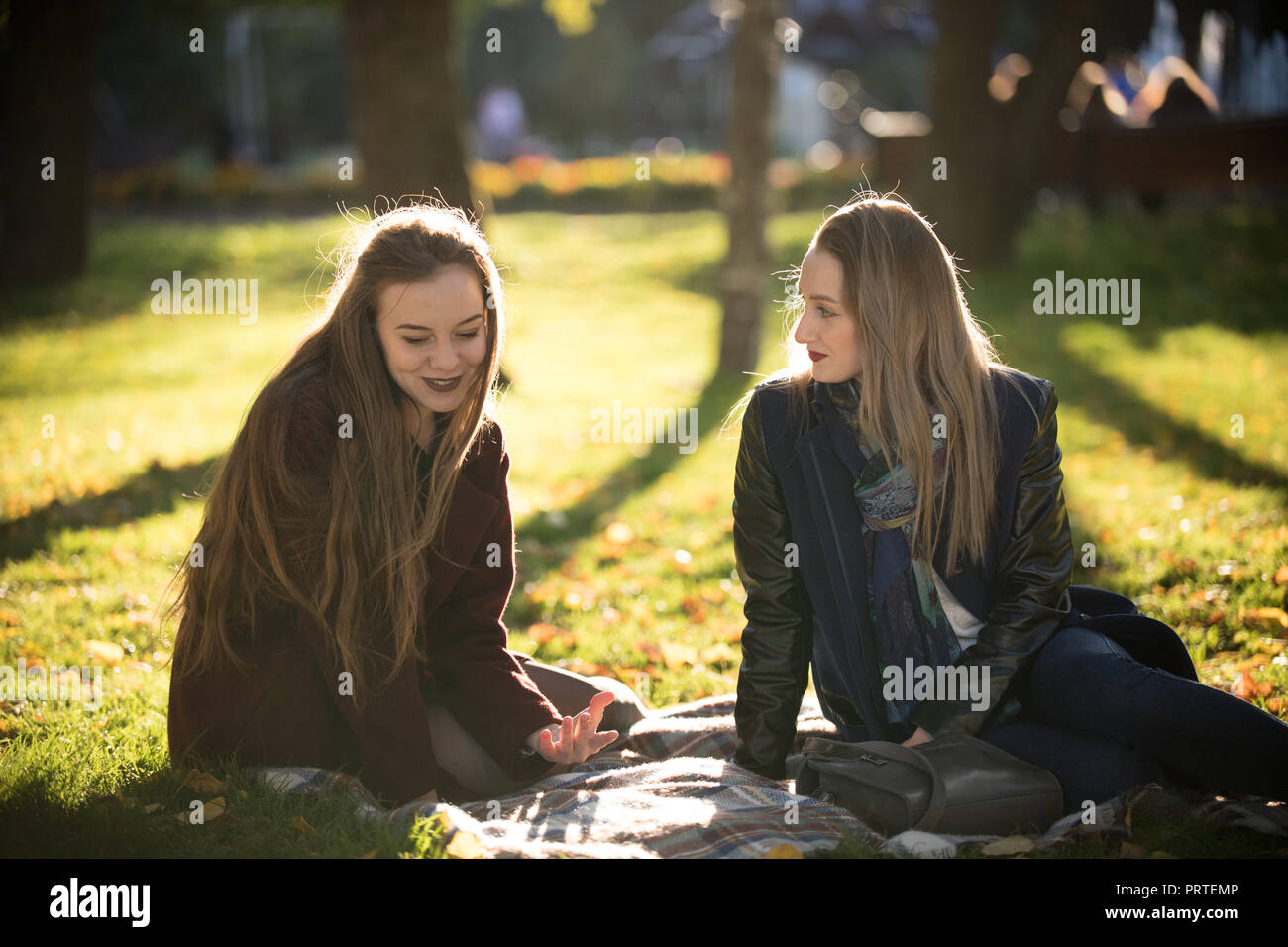 ad9e01c96 Two pretty girls in coats talking sitting on a plaid in autumn park ...