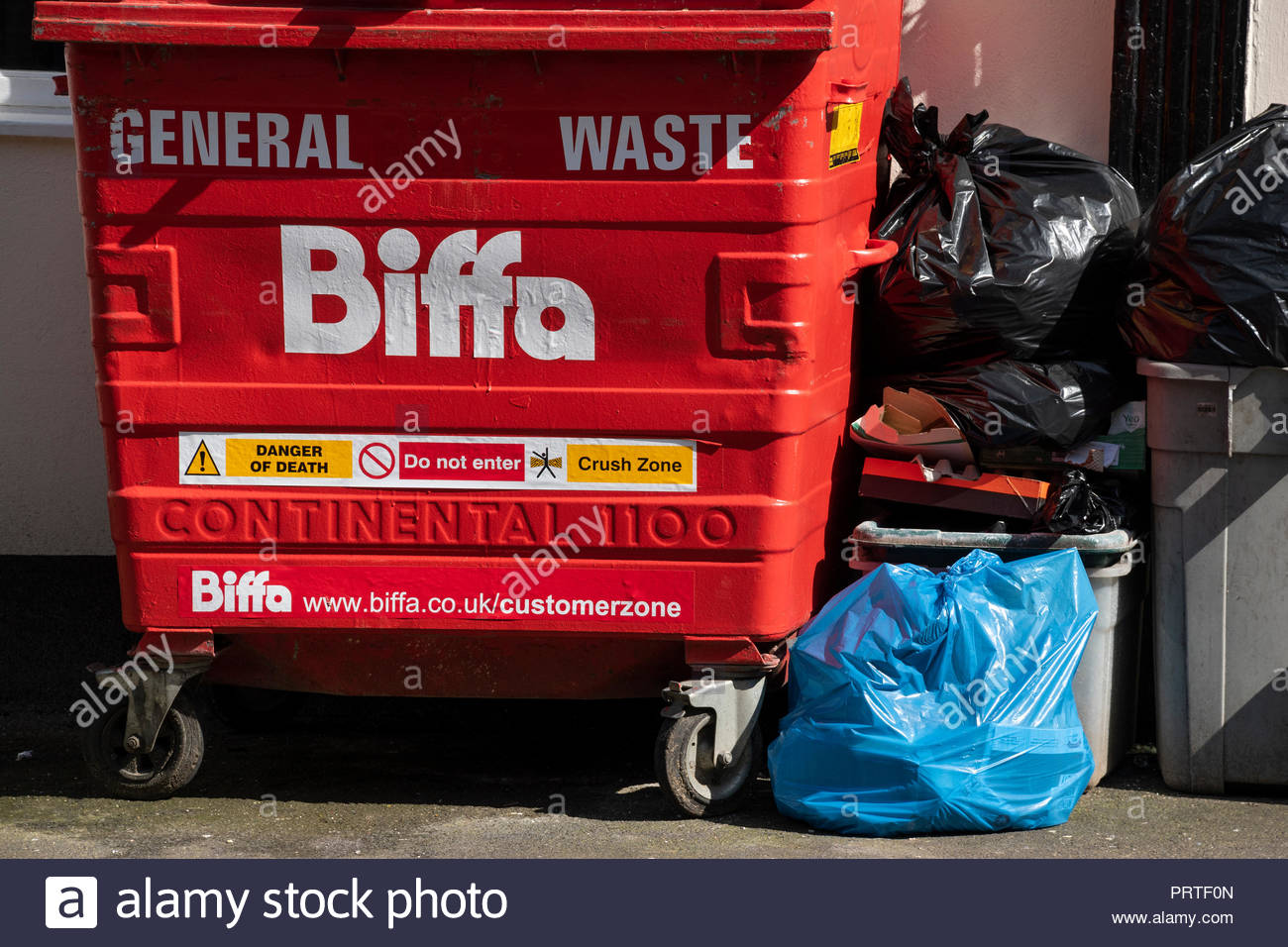 Street scene of a Biffa Gerneral Waste skip with rubbish piled by the side, Weymouth, Dorset, England, UK - Stock Image