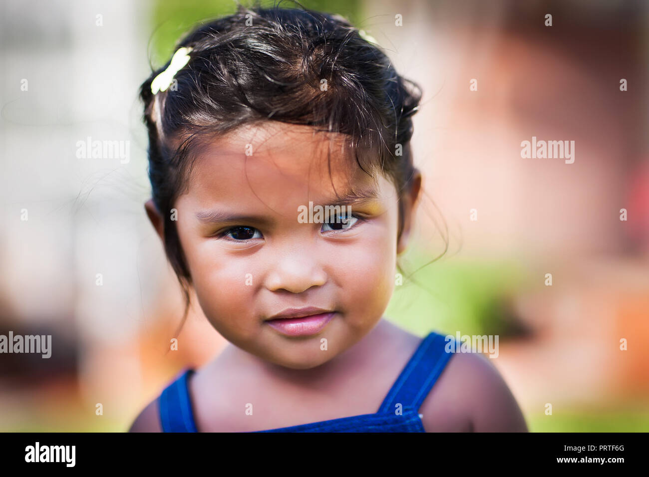 Cute little girl with thoughtful look and subtle smile - Stock Image