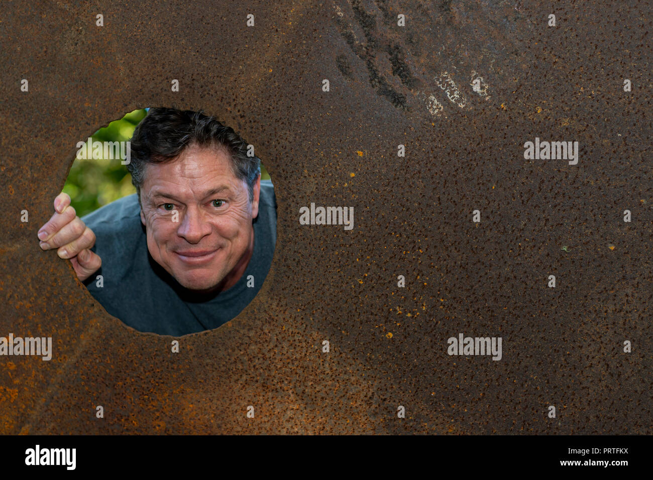 Handsome mature man in the iron plate hole, looking away, grins, happy, contented, nature background with a copy of the space, for advertising. - Stock Image